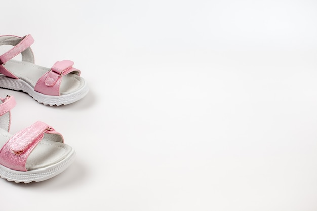 Pink childrens sandals made of shiny leather with velcro fasteners flat white soles isolated on a wh...
