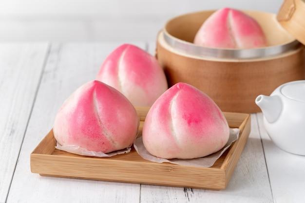 白いテーブルの背景にshoutaoという名前のピンクの中国の桃の誕生日パン。
