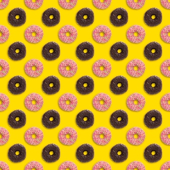 Pink and chocolate donuts with sprinkles seamless pattern on a yellow background