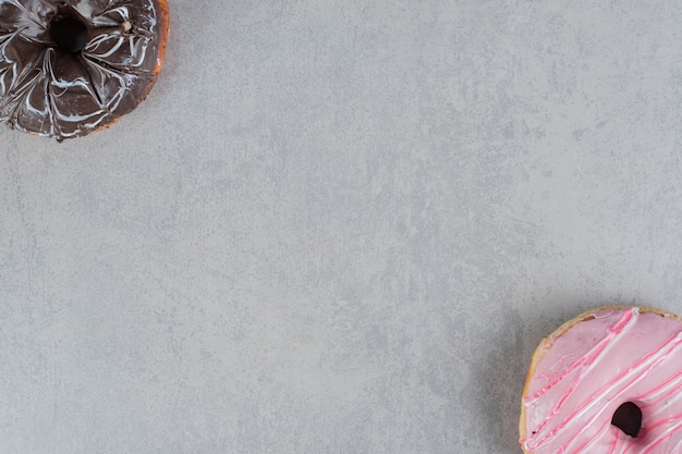 Ciambelle rosa e cioccolato su una superficie di cemento
