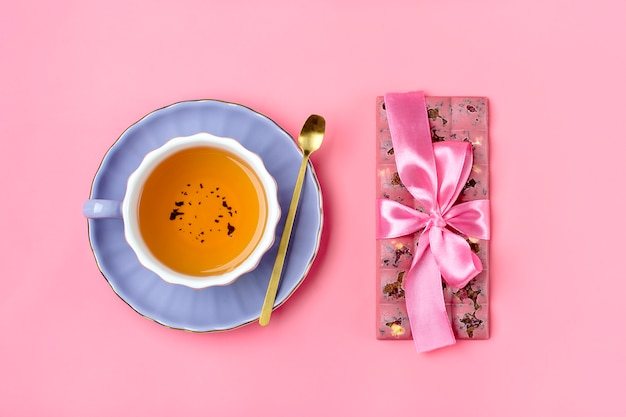 Pink chocolate with raisins and nuts on lilac plate, cup of black tea, golden spoon on pink