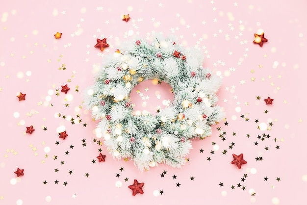 Pink christmas background. christmas wreath with decoration on pink backdrop