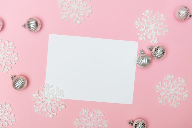 Pink christmas background with snowflakes decoration balls and empty blank for text flat lay copy space