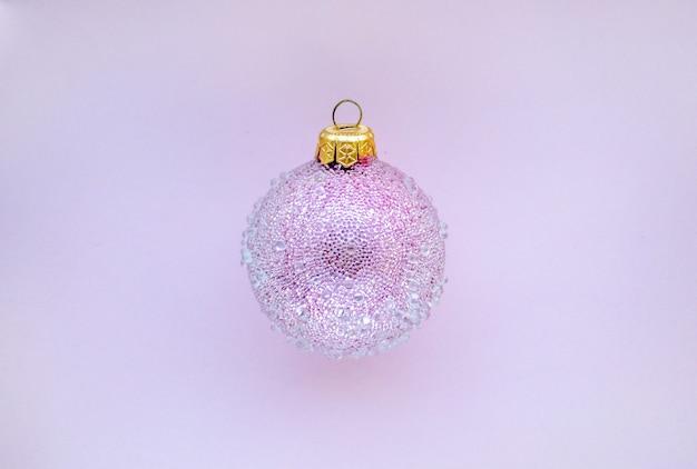 Розовый рождественский шар с некоторыми шишками на розовом фоне минималистичный рождественский дизайн место для текста