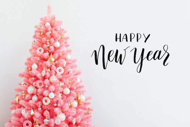 ピンクのクリスマスツリーとクリスマスの装飾の白と金色。クリスマスの背景。明けましておめでとうとクリスマスのクリスマスのコンセプト。