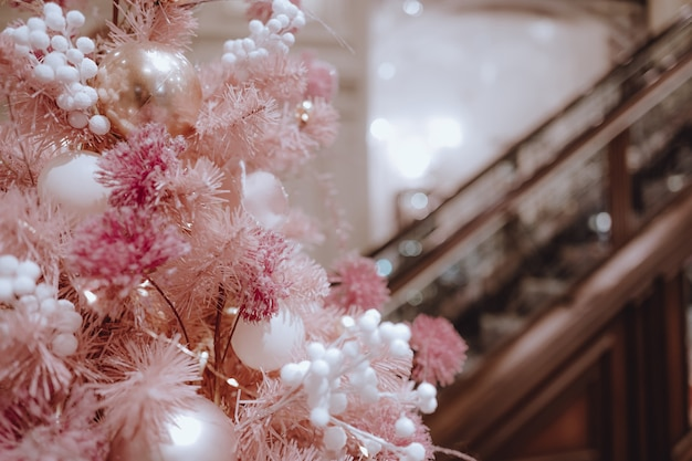 Розовая елка с сияющими шарами в праздничном интерьере