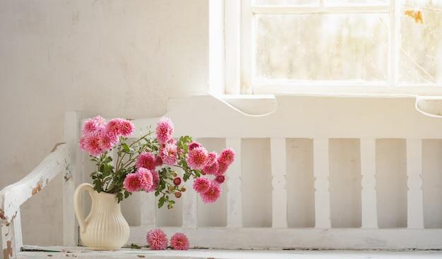 Розовые хризантемы в кувшине на старой белой деревянной скамейке