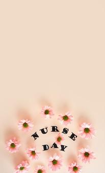 パステルピンクの背景にピンクの菊とコピースペース花柄のスタイリッシュな文字の上面図
