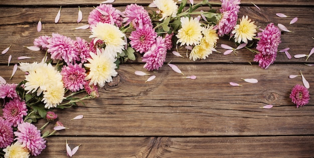 Розовые хризантемы на темном деревянном фоне