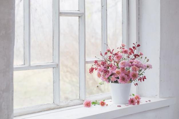 Розовые хризантемы на белом старом подоконнике