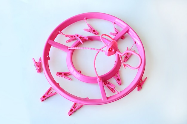 Pink circle plastic clothespins on white background.