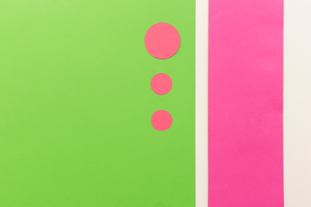 Pink circle shape papers in different sizes arranged on green card paper