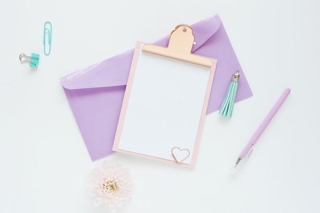 ライラックの封筒、ペン、花、白いテーブルの上のペーパークリップにピンクのクリップボード。