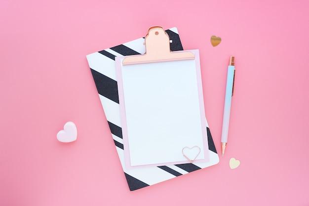 ピンクのクリップボード、ペン、ペーパークリップ、ストライプのノート、ピンクのテーブルの心。フラットなレイアウト、トップビュー。