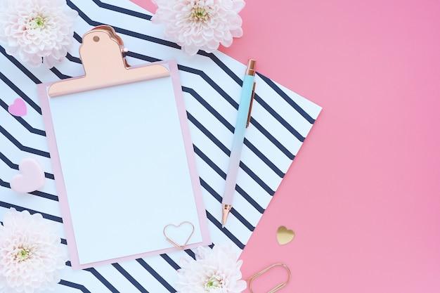 ピンクのクリップボード、ペン、ペーパークリップ、縞模様の紙、ピンクのテーブルの菊の花。フラットなレイアウト、トップビュー。