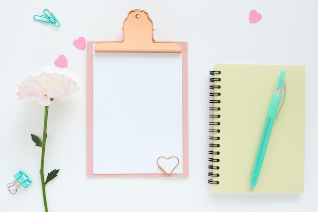 Pink clipboard, yellow notebook on a spring, pink chrysanthemum flower, blue pen, paper clips and plastic hearts.