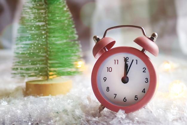 ピンクの時計、クリスマスツリーとボケ味のお祝いのぼやけた背景に対して