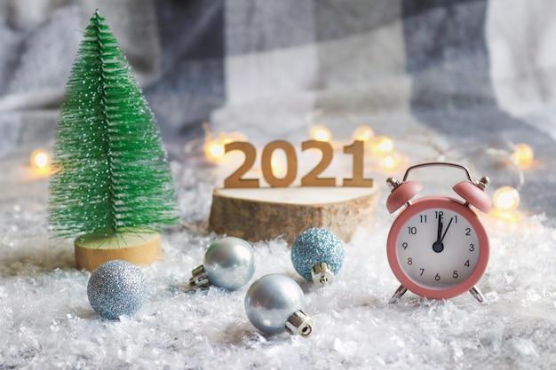 ピンクの時計、お祝いのぼやけた背景、クリスマスツリーと木製の数字に対するクリスマスボール