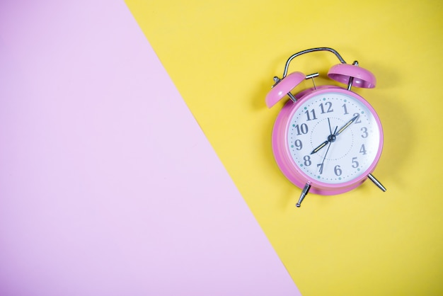 Pink clock on the colorful background, education concept