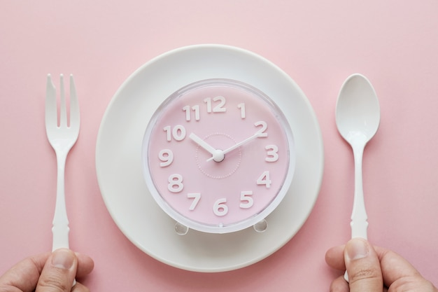 Pink clock on white plate and hands holding spoon and fork
