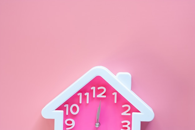Pink clock with home shape at 12 o'clock on pink background