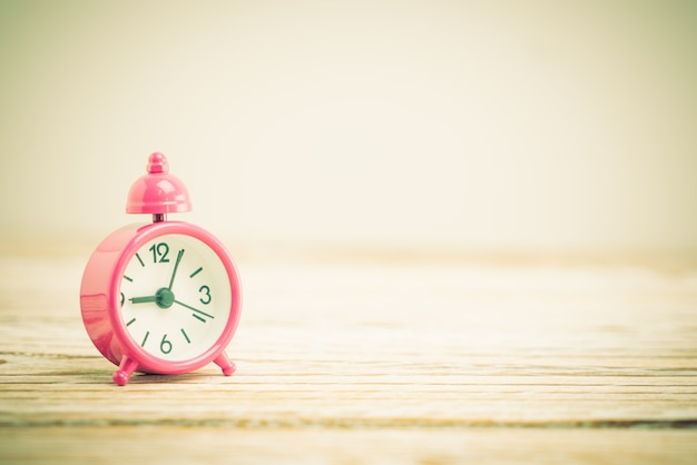 Pink clock on wooden table