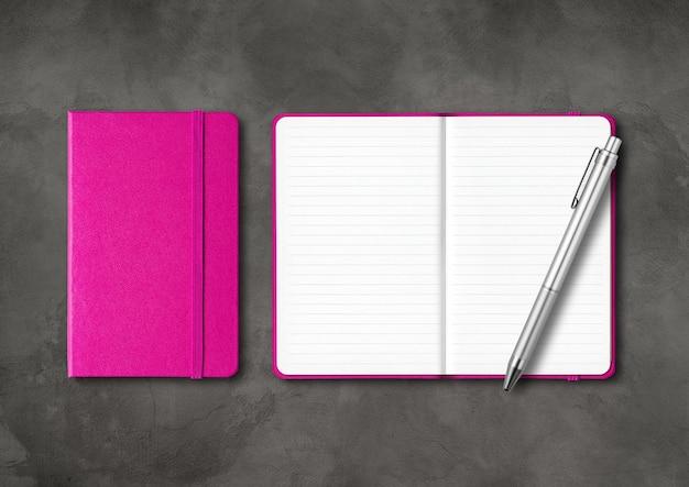 ペンでピンクの閉じた、開いた裏地付きノートブック。暗いコンクリートの背景に分離されたモックアップ