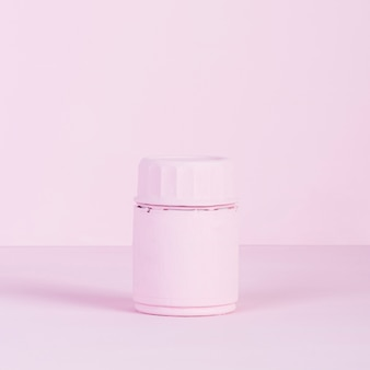 Pink closed bottle on pink background