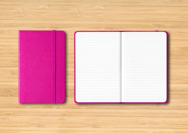 Pink closed and open lined notebooks mockup isolated on wooden background