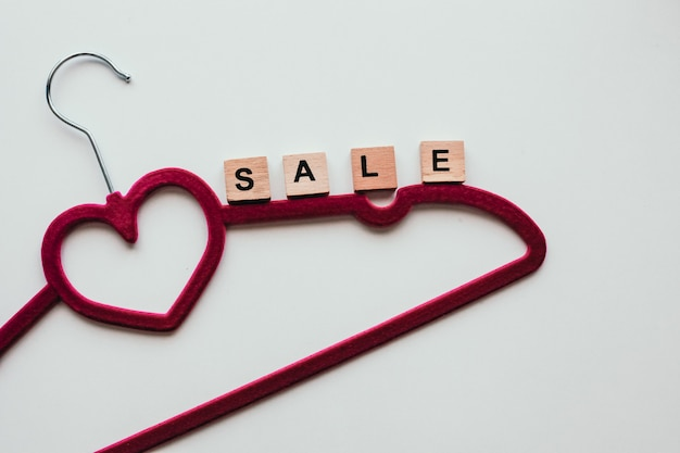 Pink clothing hanger on the white background with the word sale.
