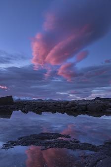 ノルウェー、ロフォーテン諸島の湖に映るピンクの雲