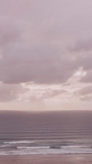 바다 위에 분홍색 흐린 하늘