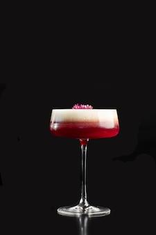 거품과 꽃 장식 레이어가 있는 쿠페 글라스의 핑크 클로버 클럽 칵테일