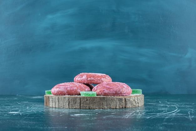 Biscotti e marmellate rivestiti rosa su una tavola di legno sul blu.