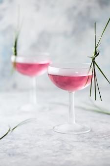 Розовый коктейль крупным планом. напиток с розовым и просекко-вином в посуде. порция экзотического французского коктейля с колотым льдом в стеклянной посуде