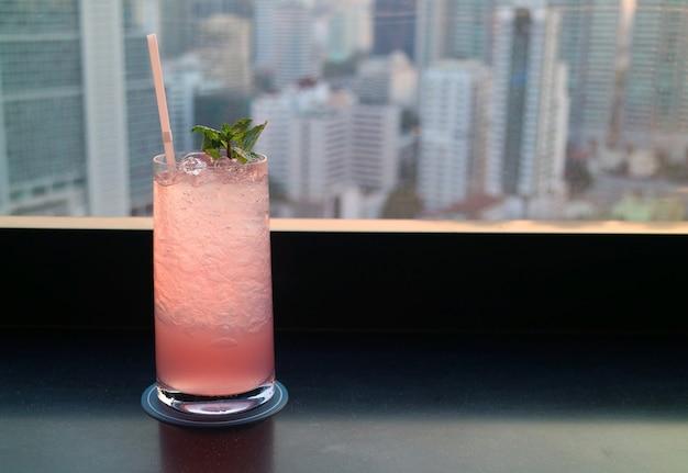 Розовый коктейль на террасе на крыше с видом на небоскребы на заднем плане