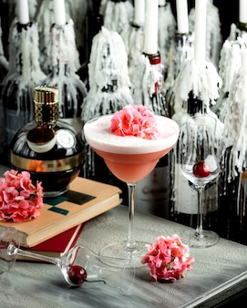 Pink cocktail in long stem glass garnished with a flower