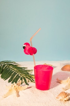 Pink cocktail on sandy beach