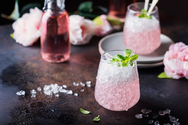 Pink cocktail with crushed ice and mint
