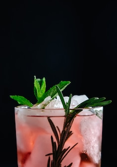 Pink cocktail with mint and rosemary on black background close-up