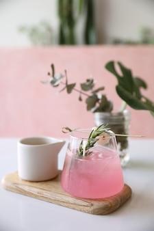 ピンクのテーブルにローズマリーとライチのピンクのカクテル