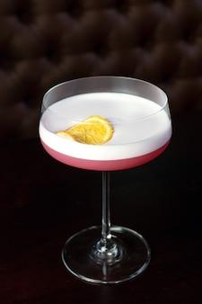 Розовые коктейли в баре на вечеринке в ночном клубе. коктейли на черном фоне в стеклянных очках.