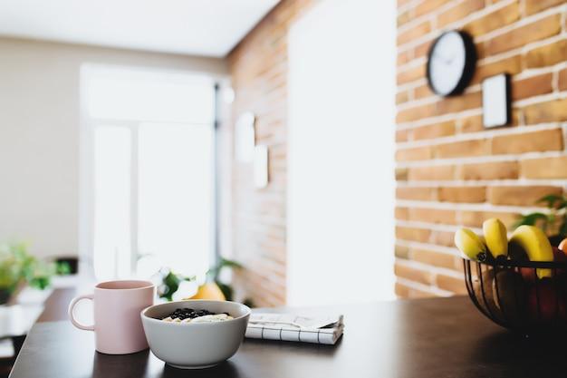 ピンクのコーヒーカップ、みじん切りのトロピカルフルーツのキウイとバナナのボウル、ブルーベリー、スタイリッシュなロフトキッチンのバーカウンターのスプーン。背景がぼやけている。高品質の写真