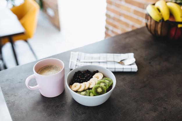 Розовая кофейная чашка, миска с нарезанными тропическими фруктами, киви и бананом, черника, ложка на барной стойке в стильной кухне-чердаке.