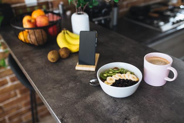 Розовая кофейная чашка, нарезанные фрукты в миске и черника, ложка, телефон на кухне