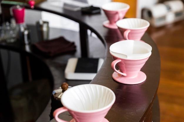 ピンクのコーヒーグラインダー、コーヒースタンド、木製のカウンターに注ぐ。