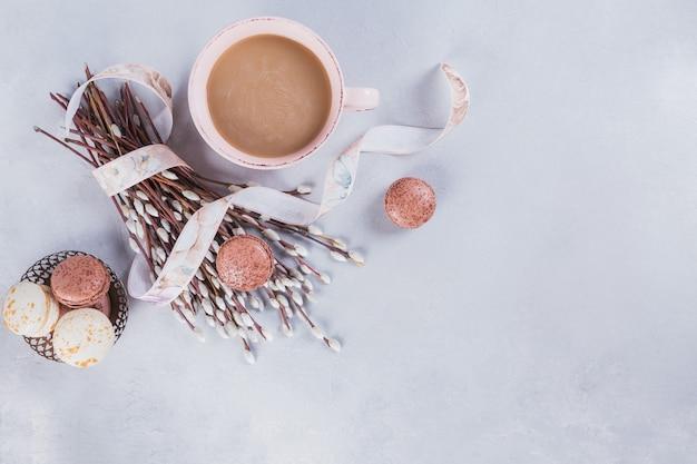 上からライトテーブルに甘いパステルフレンチマカロンとネコヤナギとピンクのコーヒーマグ