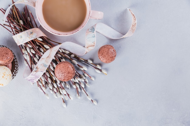 Pink coffee mug with sweet pastel french macaroons and pussy willow on light table from above