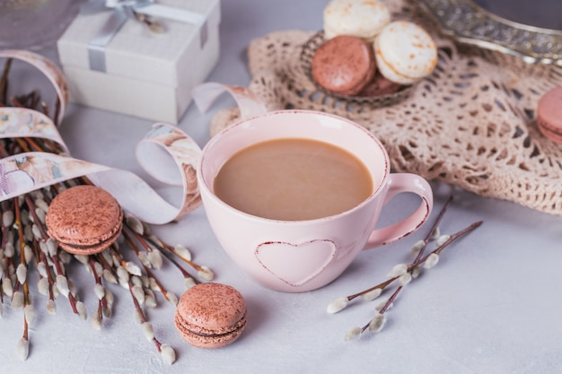 Pink coffee mug with sweet pastel french macaroons
