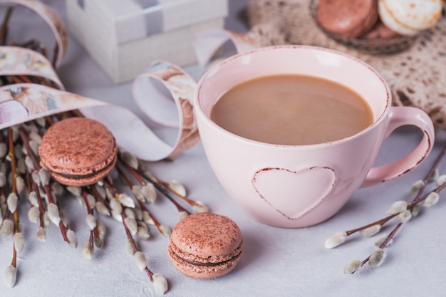 Pink coffee mug with sweet pastel french macaroons